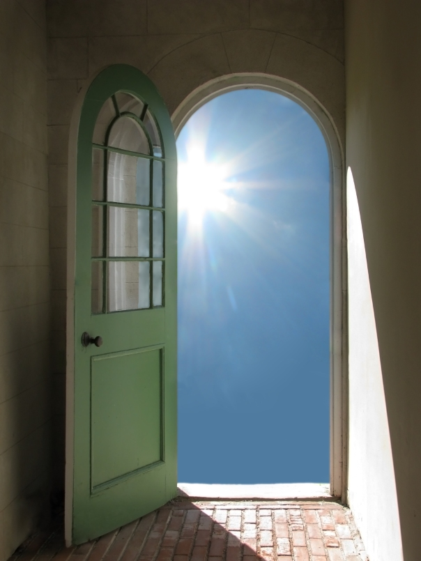 Arched doorway opening on garden stairs with sun streaming in
