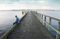 stock-photo-10302987-man-sitting-on-wharf