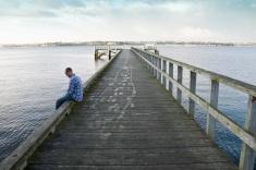 stock-photo-10302987-man-sitting-on-wharf
